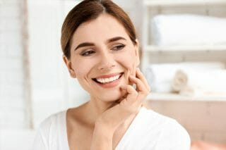 woman holding chin and smiling